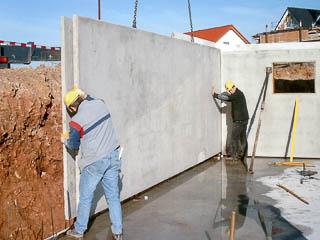 Zwei Bauarbeiter beim Absetzen einer Doppelwand.