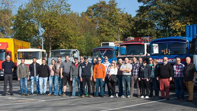 Gruppenbild vor einer Reihe von Oldtimer-LKWs.