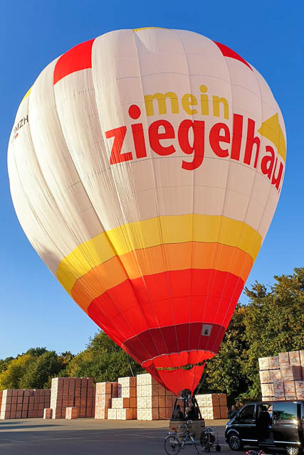Gäste der 120-Jahr-Feier besteigen den hauseigenen Heißluftballon zu einer Fahrt in abendlicher Lichtstimmung.