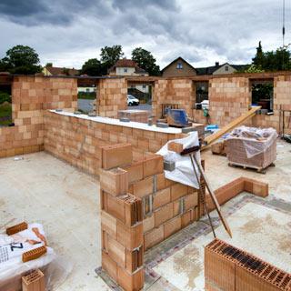 Baustelle mit unfertigem Ziegelmauerwerk. Die oberste Schicht ist mit Folie abgedeckt.