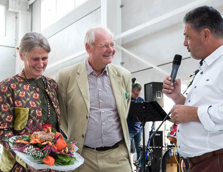 Foto: Angela Thater mit Blumenstrauß, Joachim Thater und der Betriebsratsvorsitzende Ingo Schmidt mit Mikrofon, der dem Ehepaar Thater zur neuen Beton-Fertigteil-Halle gratuliert.