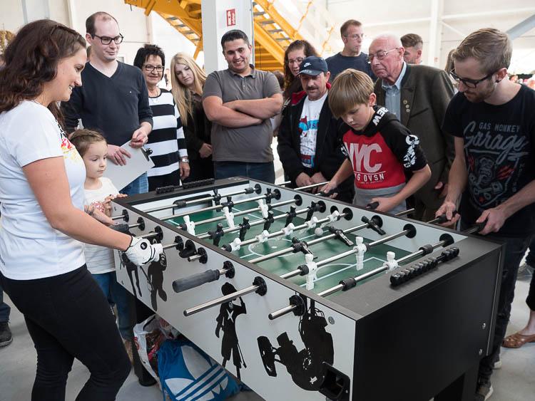 Foto: Die Europameisterin Maura Porrmann beim Kickern gegen zwei Herausforderer umringt von weiteren Gästen, die das Spiel mit Spannung verfolgen.