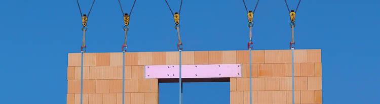 Foto Ziegelelement vor blauem Himmel an Seilkontruktion in der Luft schwebend